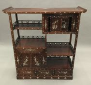 A Chinese mother-of-pearl inlaid hardwood side cabinet. 122 cm high, 114 cm wide, 37 cm deep.