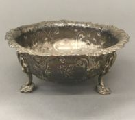 A silver embossed three footed bowl (4.