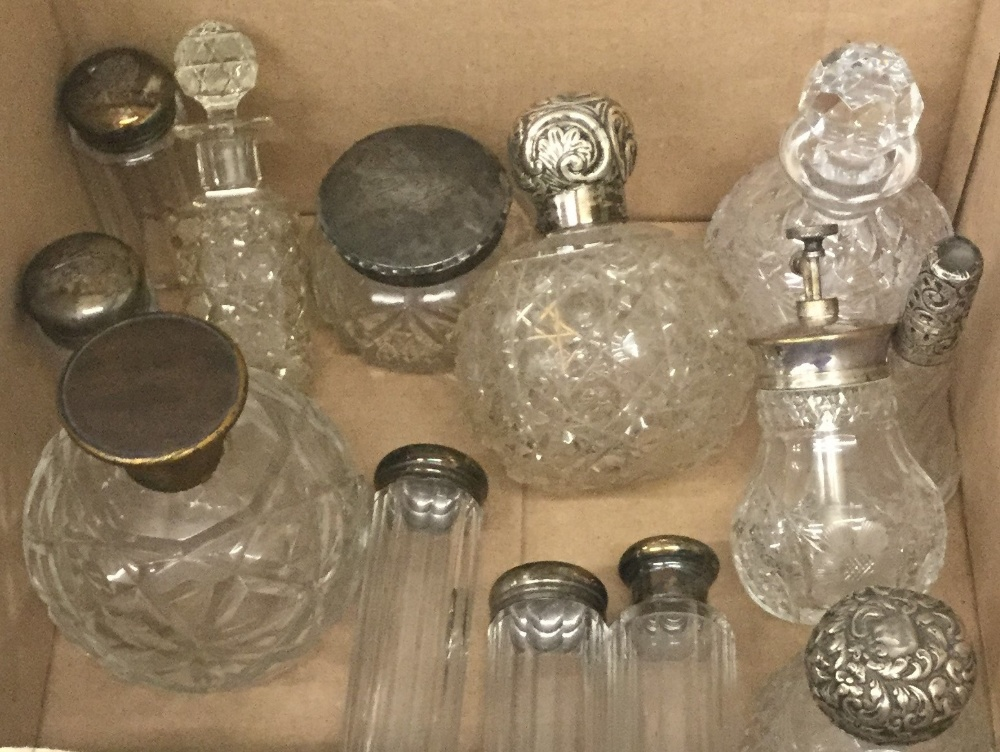 Lot 33 - A collection of various silver topped scent bottles and other glass scent bottles and jars