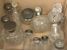A collection of various silver topped scent bottles and other glass scent bottles and jars