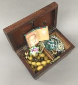 A tea caddy containing a quantity of miscellaneous costume jewellery, etc.