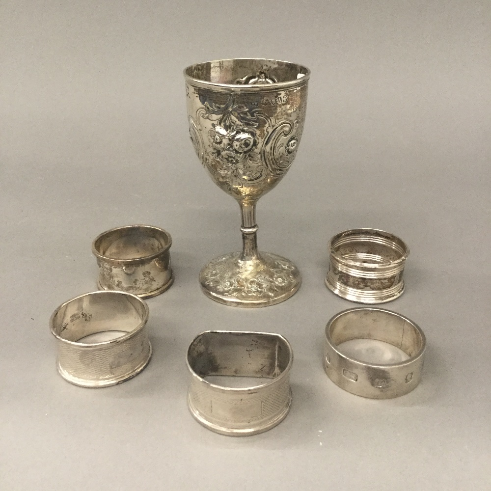 Lot 41 - Five silver napkin rings and a small embossed silver cup (6.7 troy ounces.