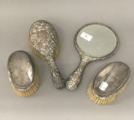 Three silver backed brushes and a silver backed mirror