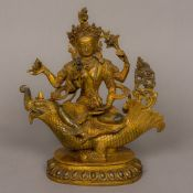 A coral and turquoise cabochon set gilt bronze model of a four armed deity Seated on a dragon above