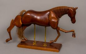 A carved wooden articulated horse Naturalistically modelled,