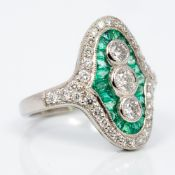 An Art Deco style platinum, diamond and emerald ring Of curved navette form,