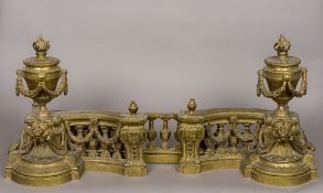 An ornate 19th century brass fire curb Each end surmounted with a flaming urn with floral swags and