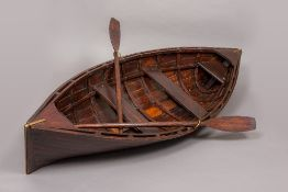 A miniature/child's hand crafted wooden rowing boat Set with brass mounts and two oars.