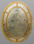 An early 19th century giltwood wall glass Of oval segmented form with central bevelled mirror plate.