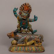 A 19th century Tibetan painted wooden carving Modelled as a deity standing on a bull's back with a