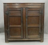 A 17th/18th century panelled oak bacon cupboard The twin plank rectangular top above twin panelled