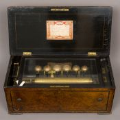 A 19th century Swiss music box The ebonised and line inlaid burr walnut case enclosing the