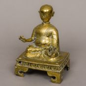 An 18th century Tibetan bronze Buddha Modelled seated in the lotus position holding a small cup and