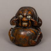 A late 19th/early 20th century Japanese carved wooden figure Modelled seated,