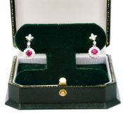 A pair of 18 ct white gold ruby and diamond drop earrings Each of flowerhead form. Each 2 cm high.