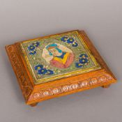 An antique Persian tile Centred with a figural bust bordered with floral sprays,