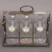 A late 19th/early 20th century silver plated three bottle tantalus Of hinged cage form,
