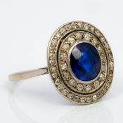 An Art Deco unmarked white gold or platinum diamond and sapphire ring Of target form. 1.6 cm high.