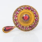 A 19th century unmarked gold garnet set brooch Of target form, set with a drop. 4.5 cm high.