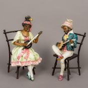 A pair of Goldscheider type porcelain figures Each modelled as a Negro musician, one male,