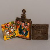 A carved wooden travelling triptych icon Of typical twin hinged form enclosing painted religious