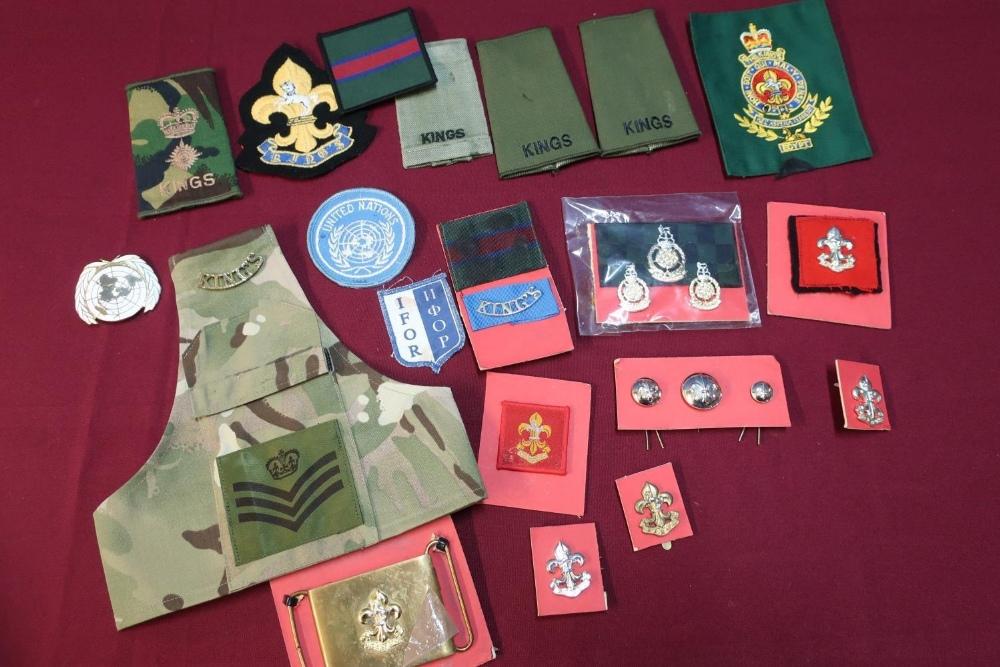 Lot 13 - Box containing a quantity of Kings regiment insignia including rank slides, cap badges, shoulder