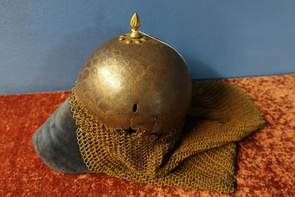 Lot 24 - 19th C Ottoman bowl shaped helmet with central finial, chain mail and face guard engraved with