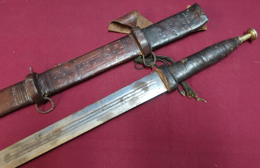 Lot 49 - North African Sudanese style sword with 31 inch double edge blade with leather bound grip and