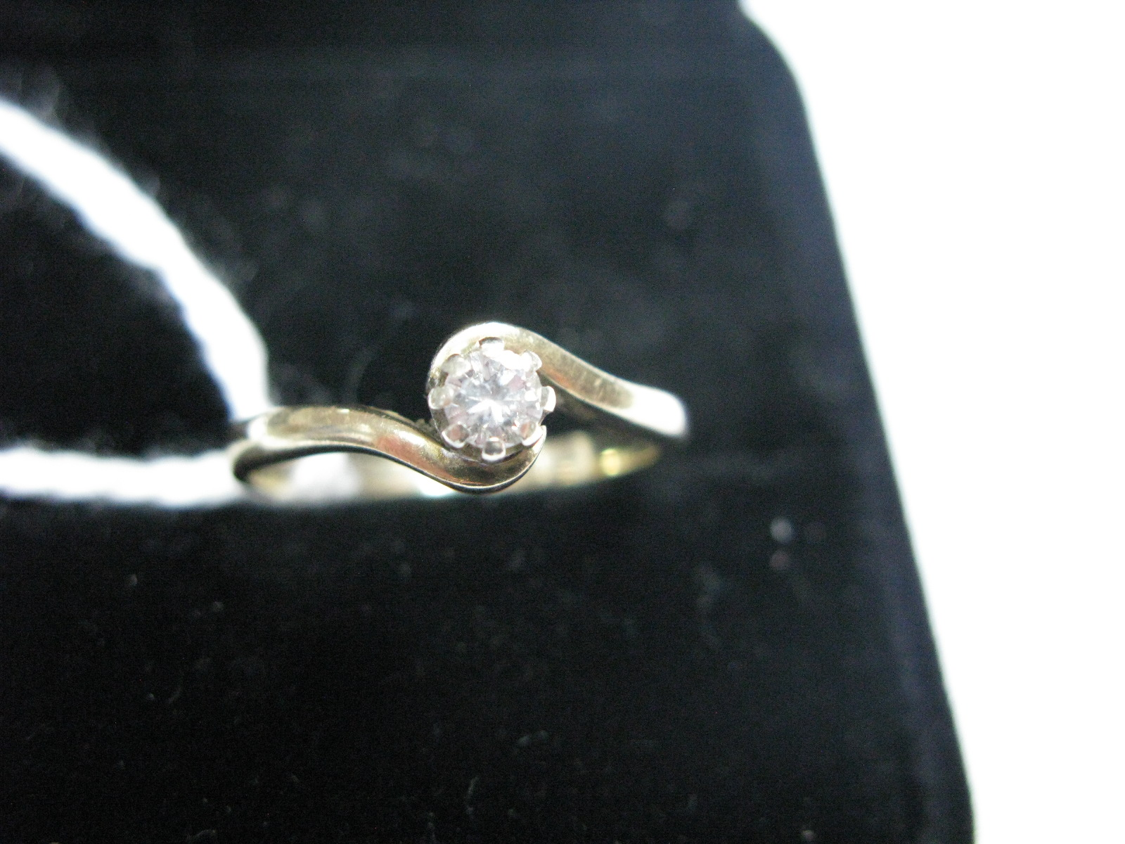 Lot 1351 - A Modern 9ct Gold Single Stone Diamond Ring, the brilliant cut stone claw set between crossover