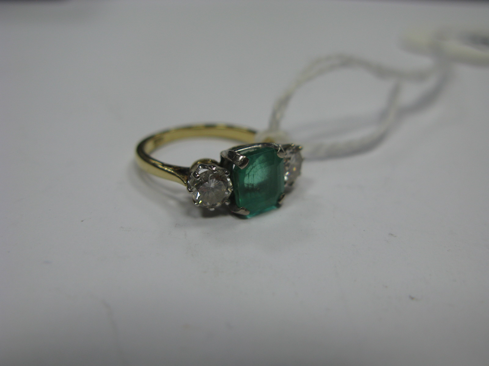 Lot 1346 - An Emerald and Diamond Three Stone Ring, square set to the centre between two claw set brilliant cut