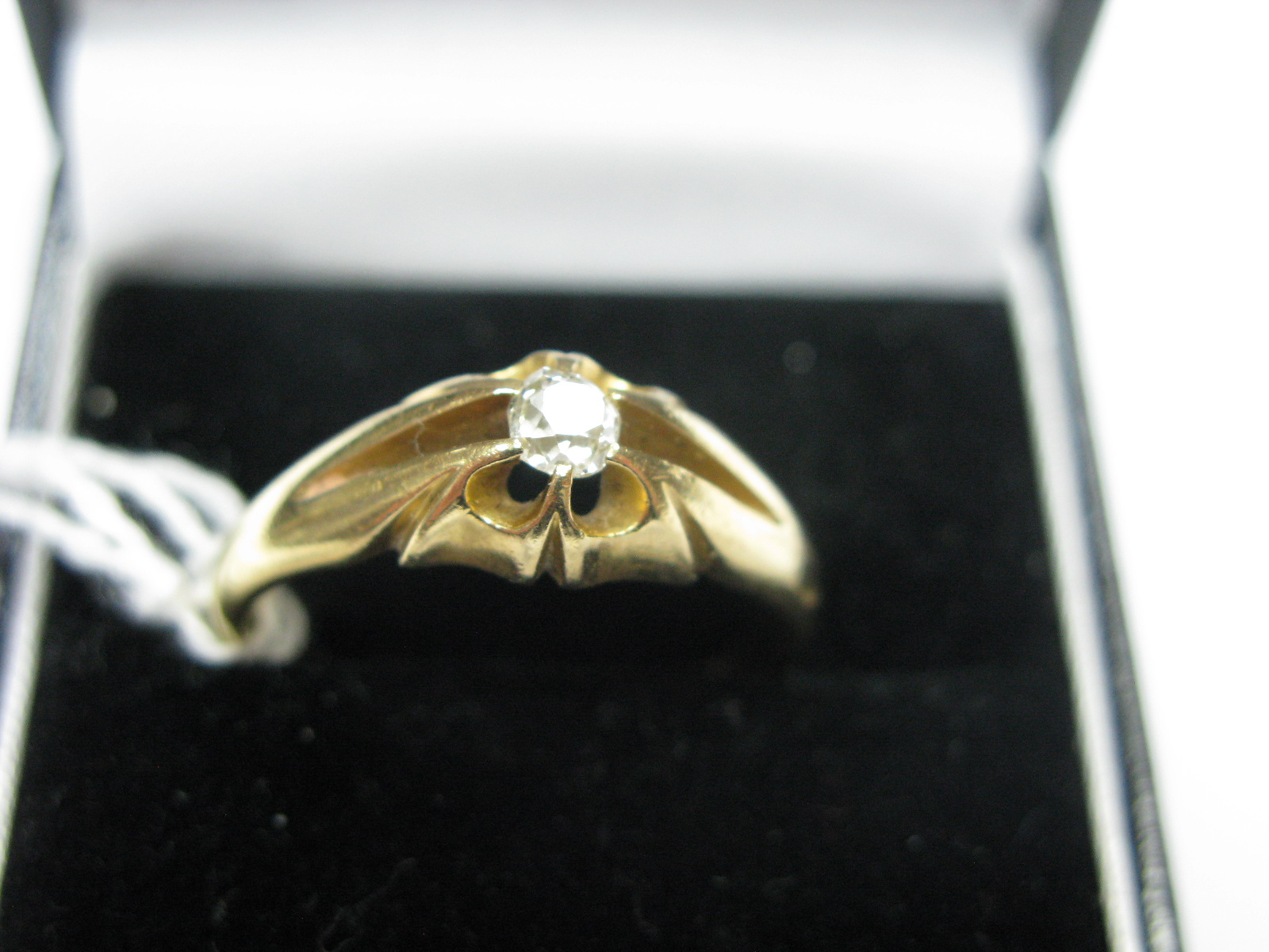 Lot 1353 - A Victorian Single Stone Diamond Ring, the old cut stone claw set between openwork shoulders.