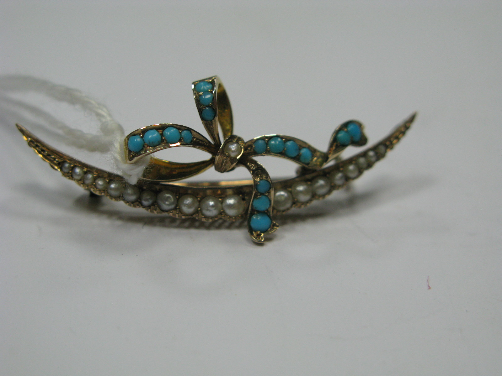 Lot 1359 - An Edwardian Turquoise and Pearl Set Bar Brooch, as a crescent with ribbon tied detail (one