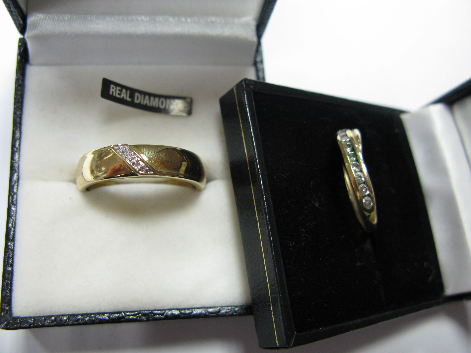 Lot 1370 - A 9ct Gold Wedding Band, with inset detail; together with another 9ct gold stone set ring. (2)