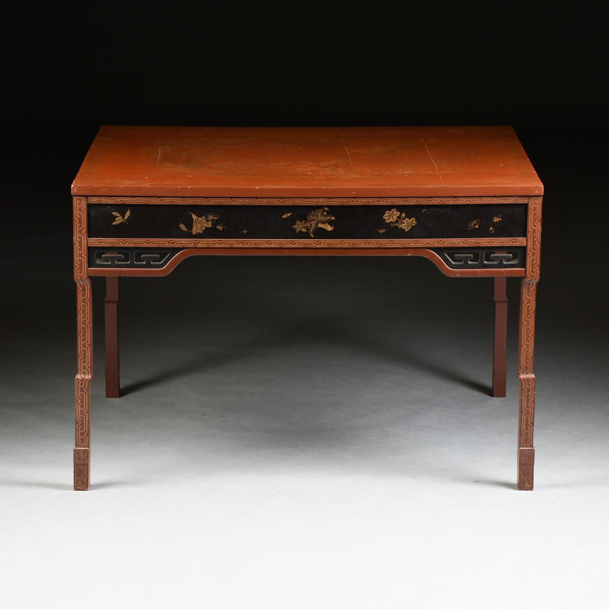 Lot 54 - A JAPANESE PARCEL GILT BURN ORANGE AND BLACK LACQUERED CENTER TABLE, SIGNED, CIRCA 1920, the