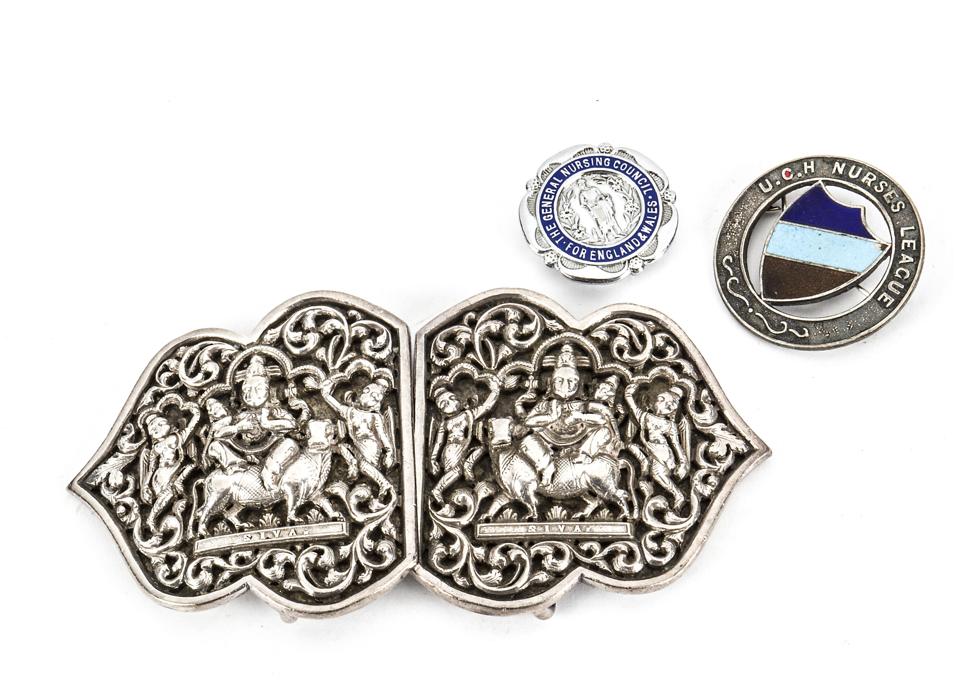 Lot 35 - A vintage Indian silver nurse's belt buckle, together with two nurse's badges (4)