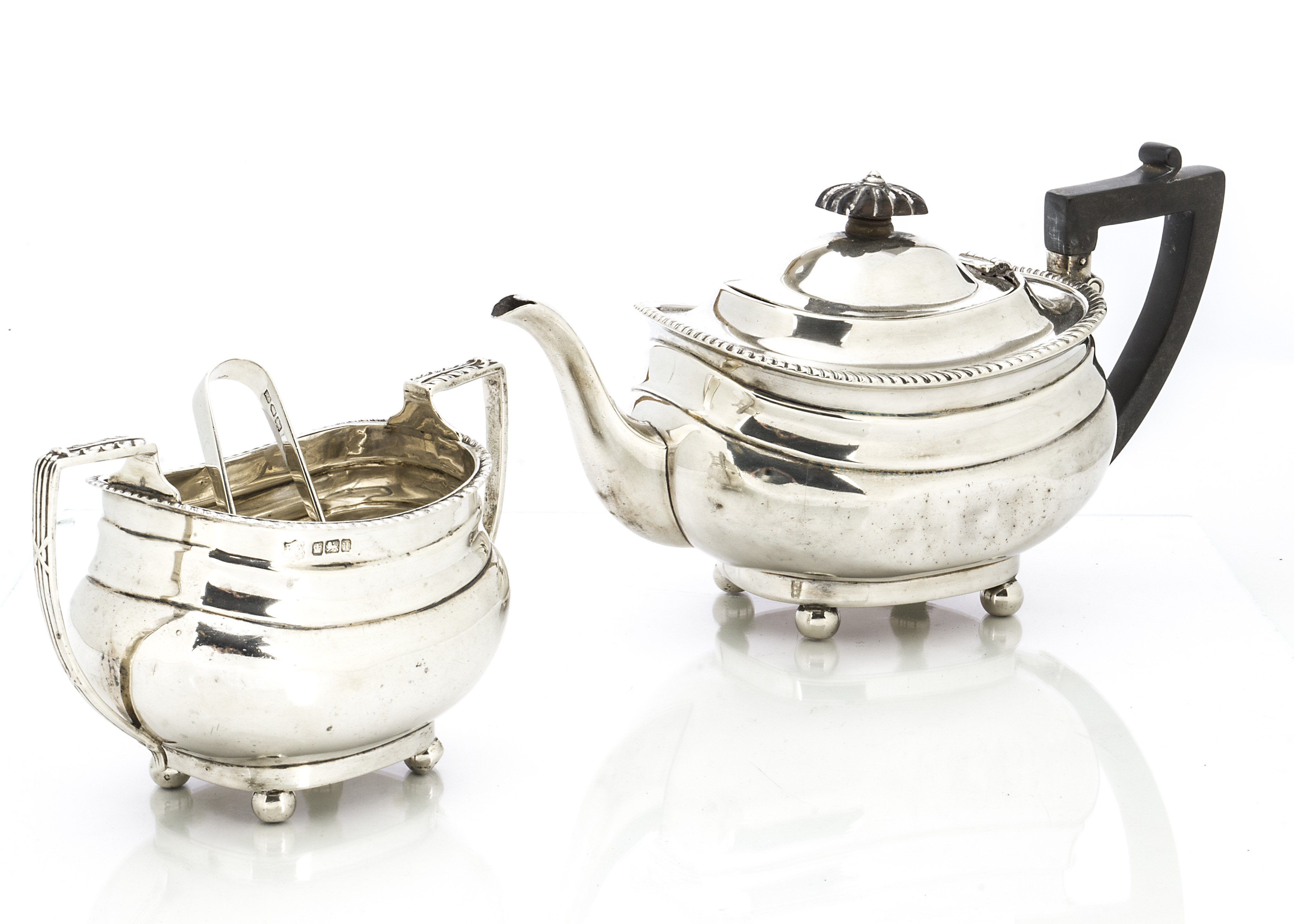 Lot 16 - An Edwardian silver teapot and sugar basin by E.W & Co, on four bun supports with gadrooned rims,