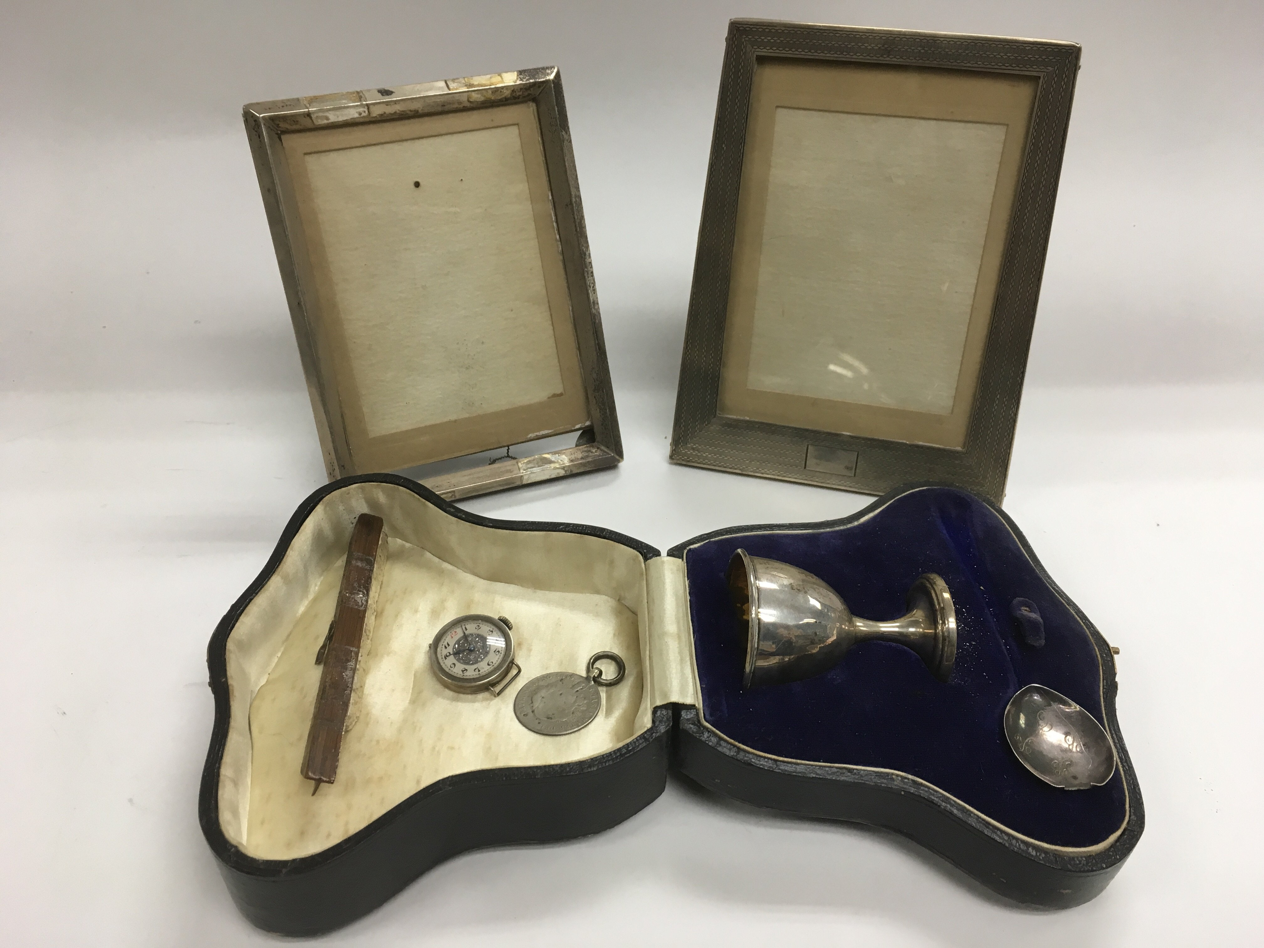 Lot 321 - A cased silver egg cup, two silver photo frames, c