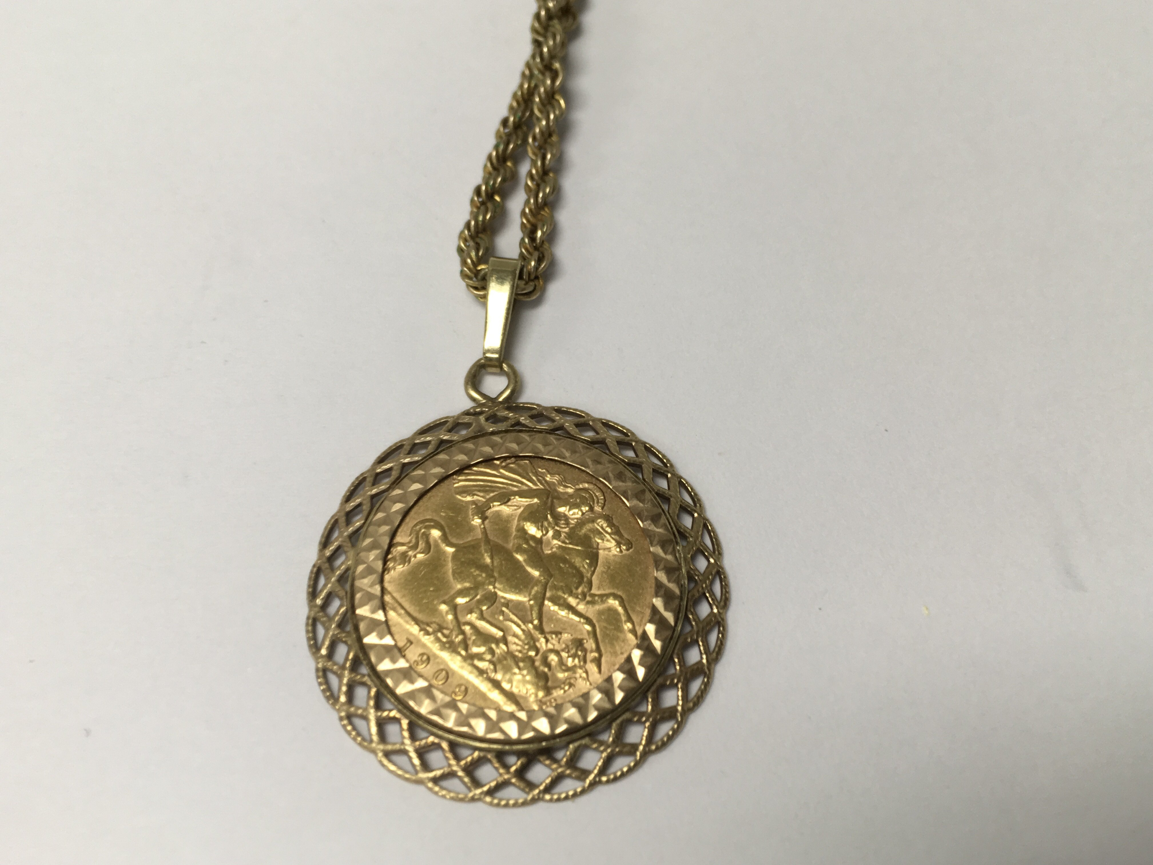 Lot 412 - A 1909 half sovereign in mount with attached chain