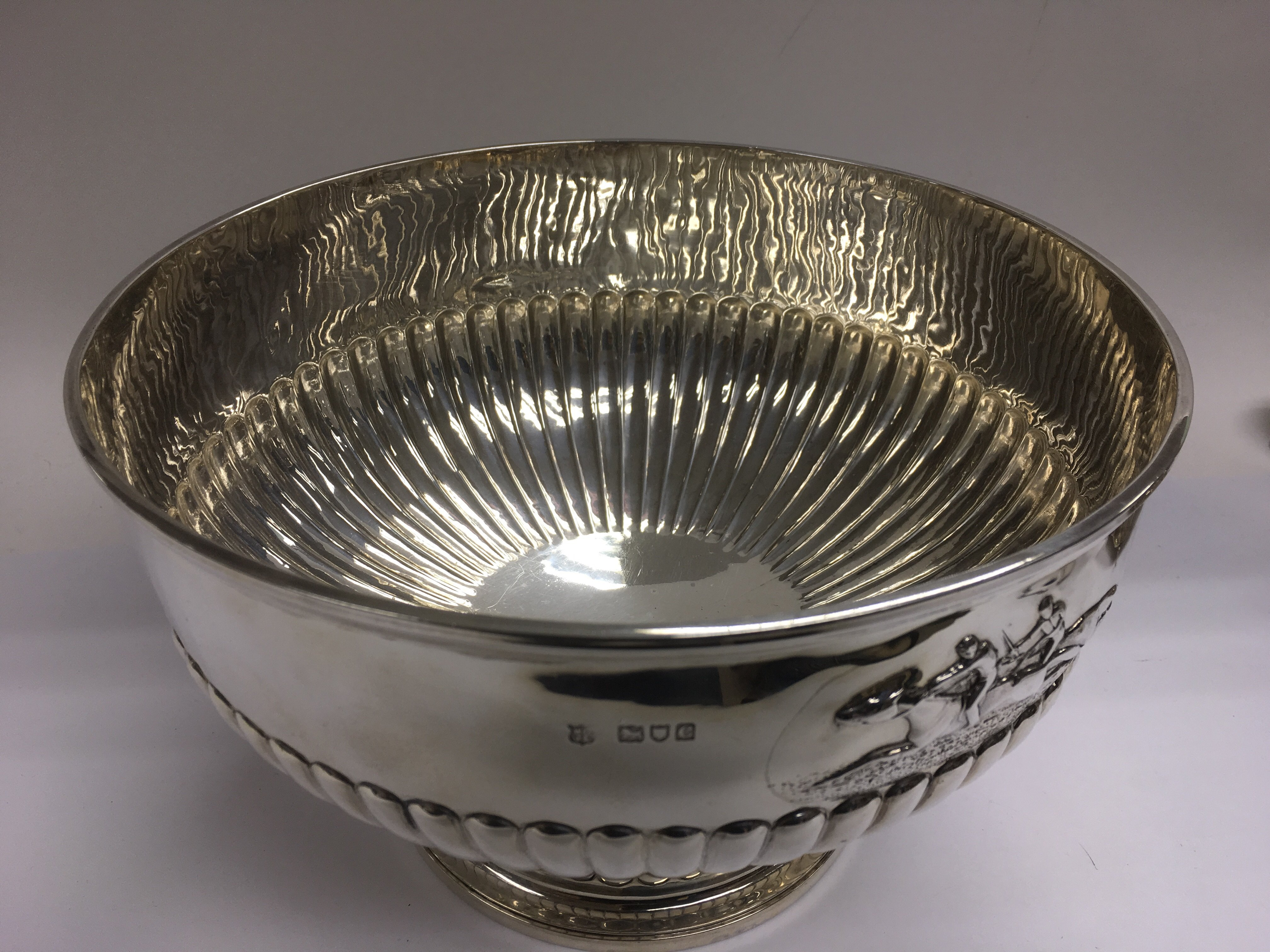 Lot 517 - A silver punchbowl with embossed horseracing decoration above a half gadrooned body, approx 1kg, app