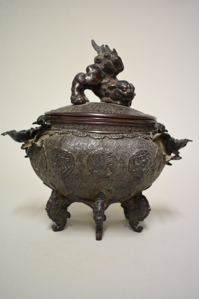 Lot 603 - An unusual Chinese bronze twin handled hexagonal censer and cover, with lion dog finial, flower head