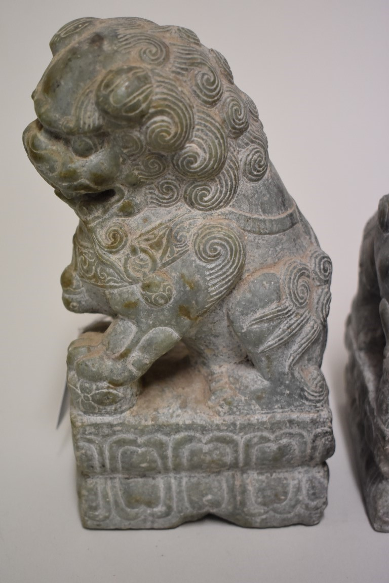 Lot 530 - A pair of Chinese green jade or soapstone lion dogs, 21.5cm high. (2)