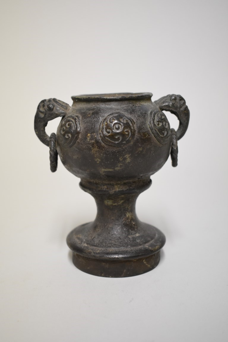 Lot 534 - An interesting and unusual Chinese Archaic twin handled dou or stem cup, relief decorated with
