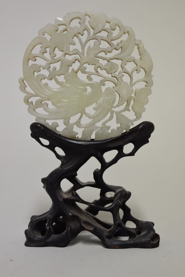 Lot 558 - A Chinese carved and pierced celadon jade roundel, decorated with a phoenix, 7.5cm diameter, on
