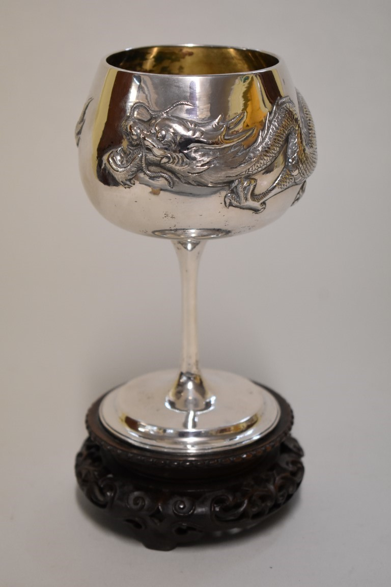Lot 574 - A Chinese silver goblet, by Wang Hing & Co, repousse decorated with a dragon, 15.5cm high, 255g,
