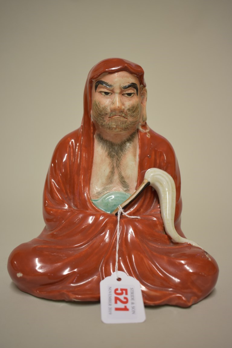 Lot 521 - A Japanese porcelain seated figure of Bodhidharma, Meiji, 21.5cm high.