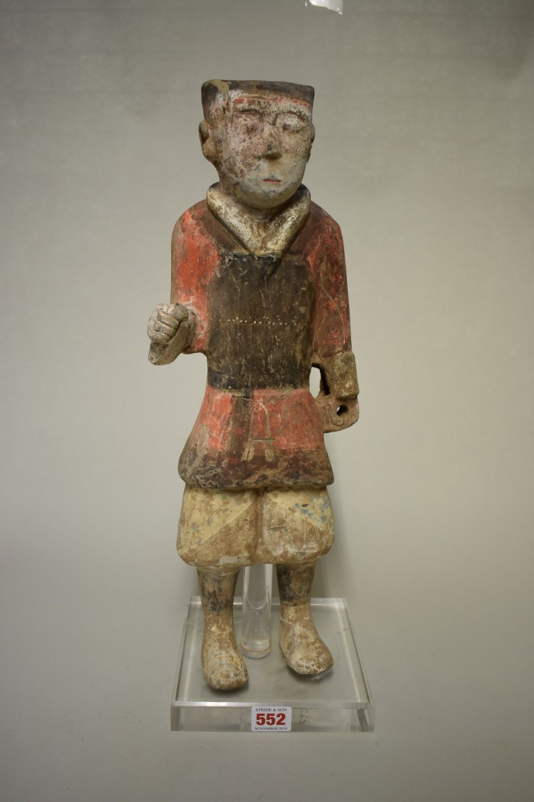 Lot 552 - A Chinese terracotta figure of a soldier, Han dynasty, with remains of painted decoration, 46.5cm