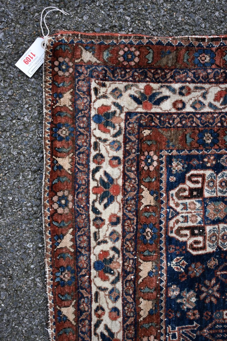 Lot 1109 - An Eastern rug,having floral and geometric design on a red and blue field, 196 x 138cm.
