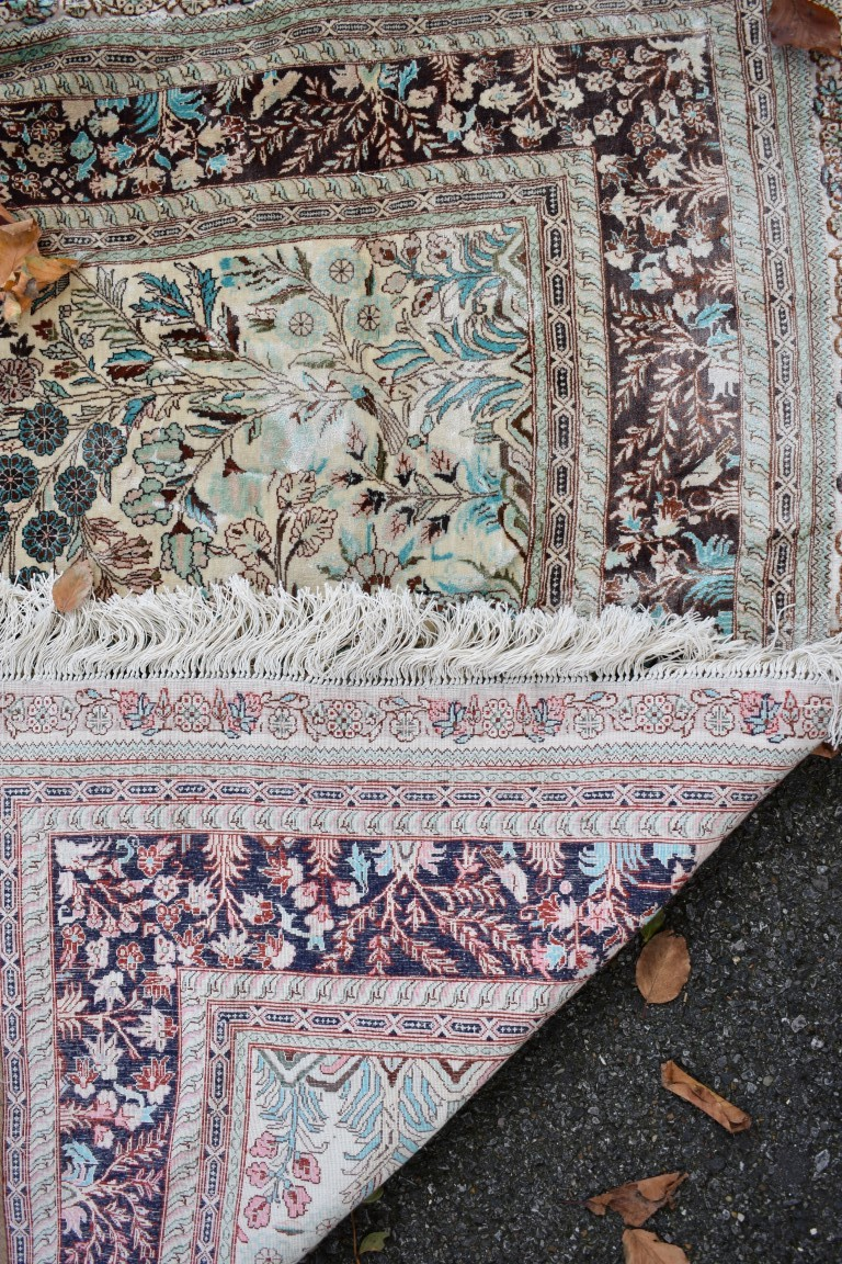 Lot 1112 - An Oriental rug,having beige field with allover floral design, 195 x 120cm.