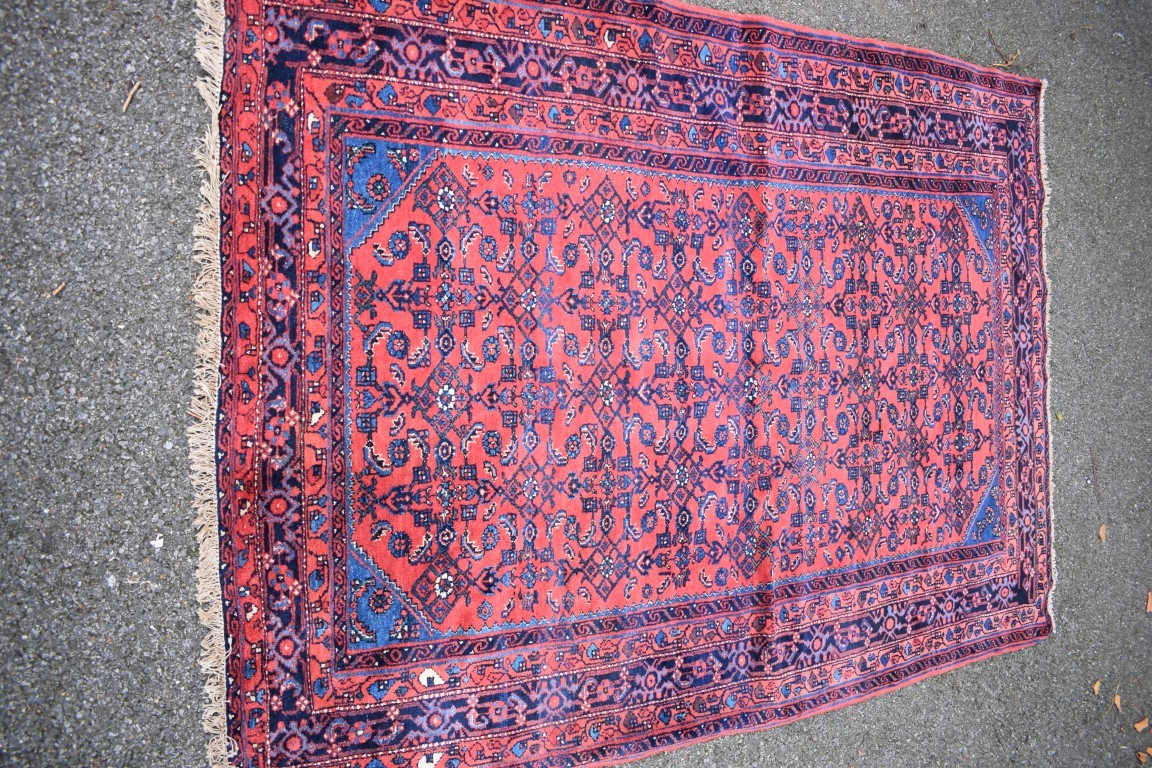 Lot 1117 - An Eastern rug,with geometric and floral design on a red field, 195 x 138cm.