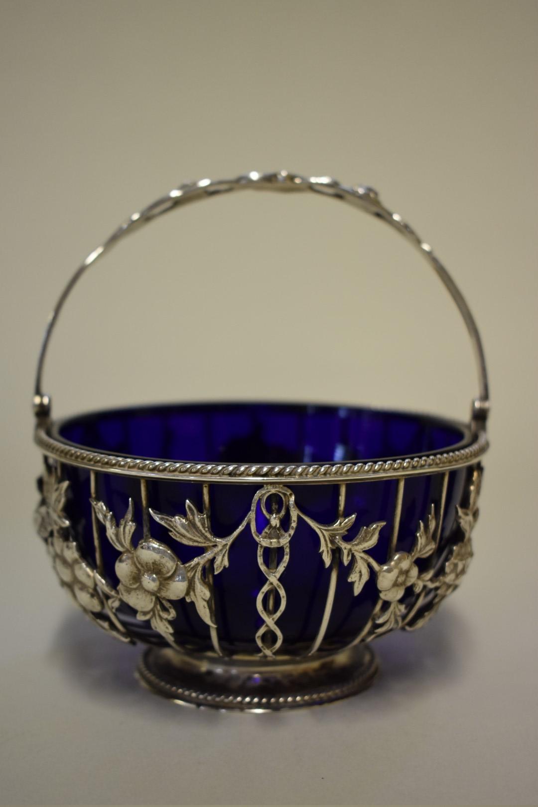 Lot 14 - A Victorian pierced silver basket,by Goldsmiths & Silversmiths Co,London 1896, having blue glass